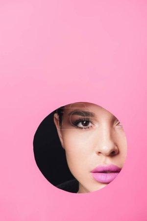 Photo pour Belle fille avec des yeux fumés et des lèvres roses regardant la caméra à travers le trou dans le papier sur noir - image libre de droit