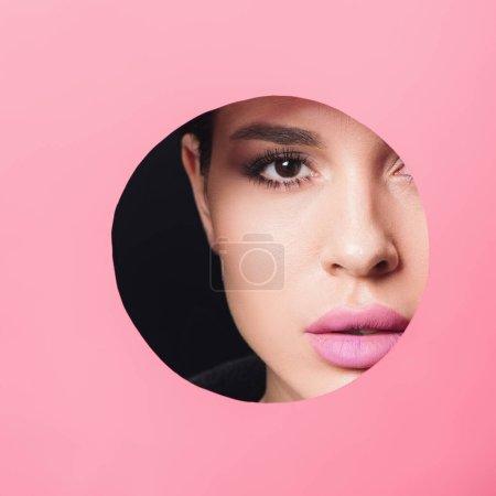Photo pour Belle fille avec des yeux fumés et des lèvres roses regardant la caméra à travers le trou dans le papier sur fond noir - image libre de droit