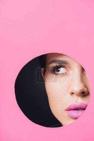 Photo pour Belle fille aux yeux fumés et aux lèvres roses regardant loin à travers un trou rond en papier sur fond noir - image libre de droit
