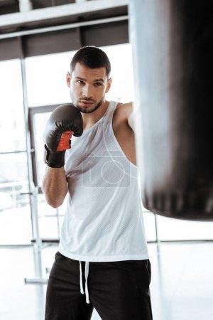 Photo pour Focus sélectif d'un bel homme dans des gants de boxe s'exerçant avec un sac à poing - image libre de droit