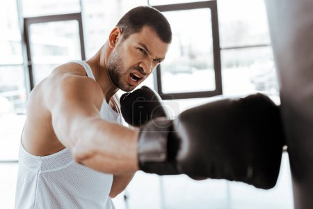 Photo for Selective focus of angry sportsman in boxing gloves exercising with punching bag - Royalty Free Image