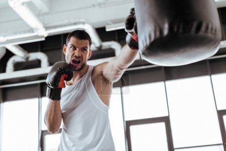 Photo pour Focalisation sélective d'un homme en colère dans des gants de boxe exercice avec un sac à main - image libre de droit