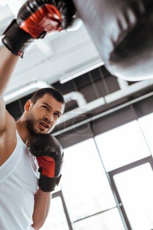 Photo pour Focalisation sélective du sportif dans des gants de boxe exercice avec sac à poing - image libre de droit