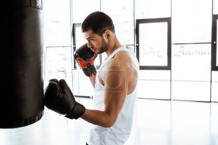Photo for Side view of handsome sportsman in boxing gloves training with punching bag in sports center - Royalty Free Image