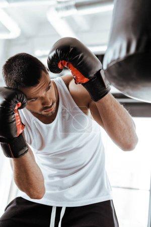 Photo pour Focalisation sélective d'un bel homme dans des gants de boxe entraînement avec un sac à découper - image libre de droit