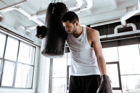 Photo pour Sportif fatigué dans des gants de boxe debout près d'un sac de boxe - image libre de droit