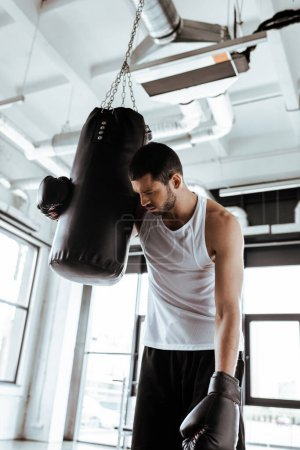 Photo pour Un sportif épuisé dans des gants de boxe debout près d'un sac perforant - image libre de droit