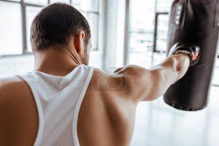 Photo pour Vue arrière du sportif dans l'entraînement des gants de boxe avec sac de boxe - image libre de droit