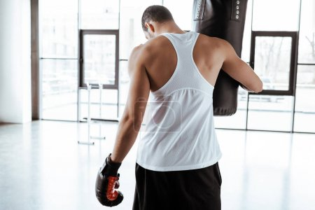 Photo pour Back view of sportsman in boxing glove touching punching bag - image libre de droit