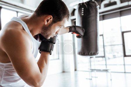 Photo pour Focalisation sélective du sportif athlétique en gants de boxe entraînement avec un sac à poinçonner - image libre de droit