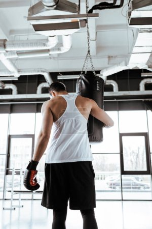 Photo pour Back view of sportsman in boxing gloves touching punching bag  while standing in sports center - image libre de droit