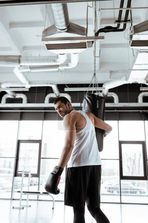 handsome sportsman looking at camera near punching bag