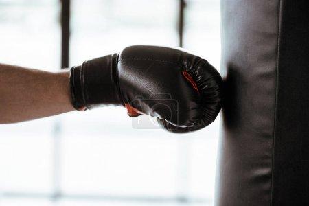 Ausgeschnittene Sicht auf Sportler beim Boxhandschuhtraining mit Boxsack
