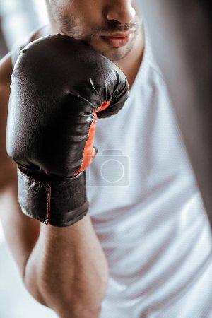Photo pour Vue recadrée du sportif en gant de boxe noir dans le centre sportif - image libre de droit
