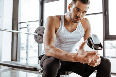 Photo for Handsome sportsman holding sports bottle with protein milkshake and looking at camera in gym - Royalty Free Image