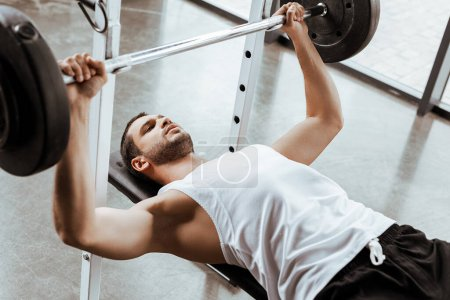 Photo for Selective focus of handsome sportsman exercising with barbell in gym - Royalty Free Image