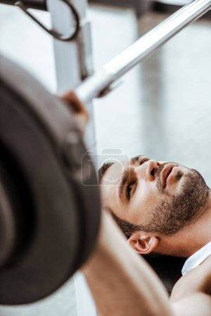 Photo for Selective focus of bearded sportsman exercising with barbell in gym - Royalty Free Image