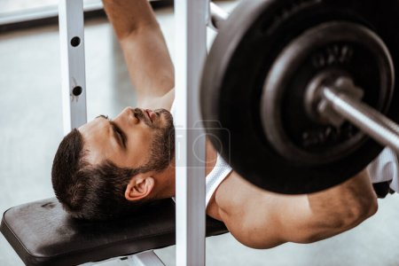 Photo for Selective focus of handsome man exercising with barbell in gym - Royalty Free Image