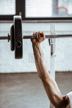 Photo for Cropped view of sportsman working out with barbell in gym - Royalty Free Image