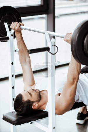 Photo for Handsome sportsman working out with barbell in gym - Royalty Free Image