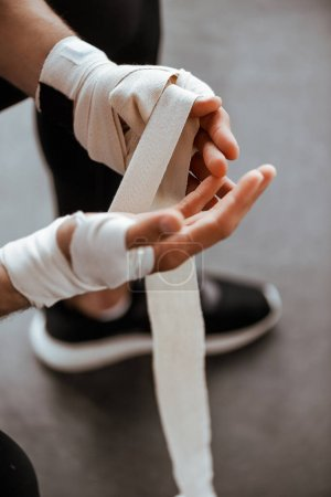 Photo pour Vue recadrée de l'homme enveloppant la main dans un bandage de sport - image libre de droit