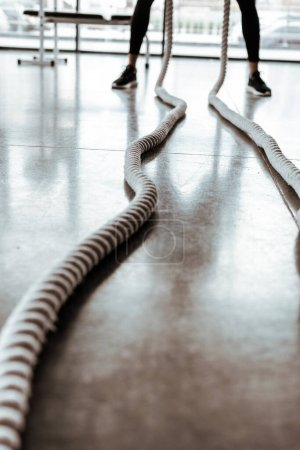 cropped view of sportsman training with battle ropes in gym
