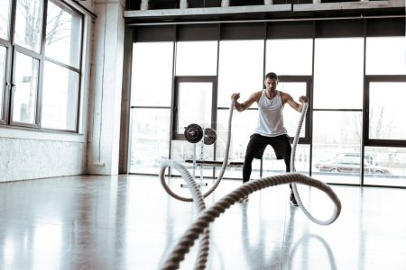 selective focus of sportsman exercising with battle ropes in modern gym