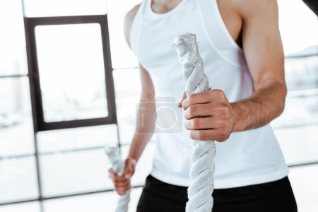 Photo for Cropped view of sportsman exercising with battle ropes in gym - Royalty Free Image