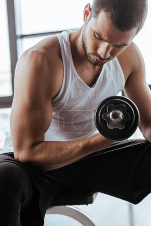 Photo for Handsome sportsman exercising with dumbbell in gym - Royalty Free Image