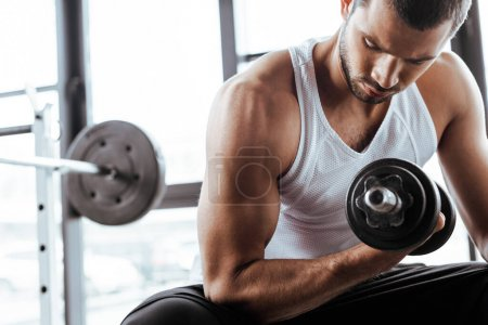 Photo for Strong sportsman exercising with dumbbell while sitting in gym - Royalty Free Image