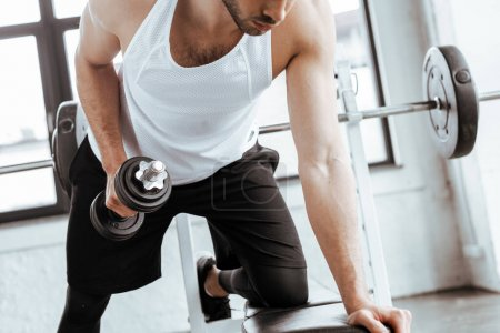Photo for Cropped view of bearded man exercising with heavy dumbbell in gym - Royalty Free Image