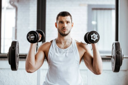 Photo pour Sportif sportif tenant des haltères tout en travaillant dans la salle de gym - image libre de droit