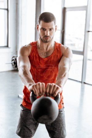selective focus of strong sportsman exercising with heavy dumbbell
