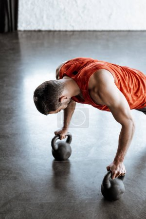 Photo for Athletic sportsman doing plank exercise with heavy dumbbells - Royalty Free Image