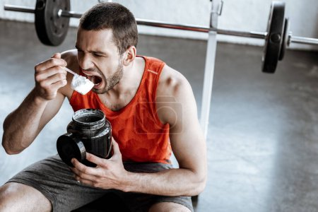 Photo for Athletic sportsman with opened mouth holding jar and measuring spoon with protein powder - Royalty Free Image