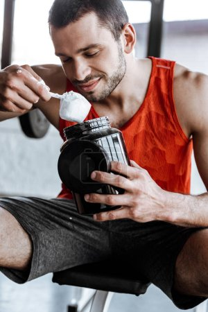Photo for Happy sportsman holding jar and looking at measuring spoon with protein powder - Royalty Free Image