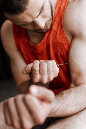 Photo for Selective focus of sportsman making doping injection - Royalty Free Image