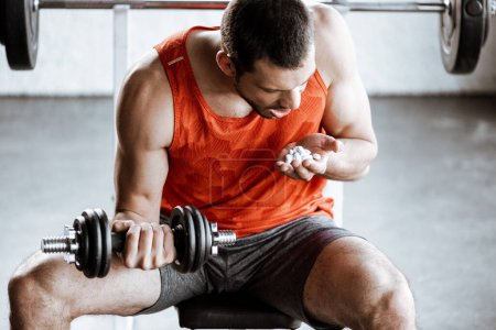 sportsman with opened mouth exercising with dumbbell and looking at probiotic pills in gym