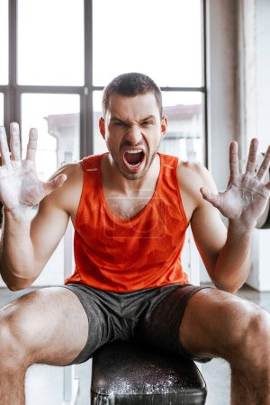 Photo for Emotional handsome sportsman with white powder on hands screaming in gym - Royalty Free Image