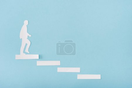 Top view of paper man on career ladder on blue background
