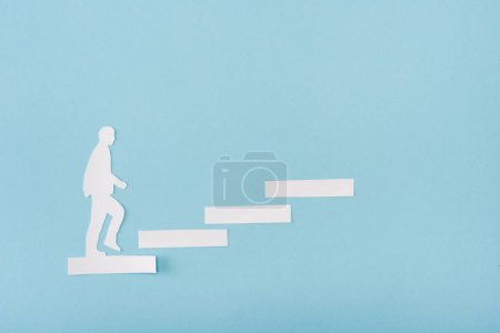 Photo for Top view of paper man on career ladder on blue - Royalty Free Image
