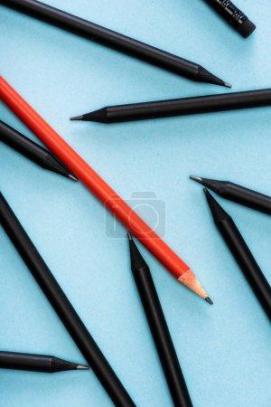 Photo pour Vue du dessus du crayon rouge unique parmi le noir sur fond bleu - image libre de droit