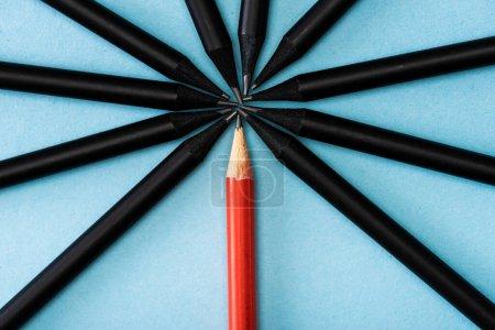 Foto de Vista superior del lápiz rojo único entre negro sobre azul. - Imagen libre de derechos