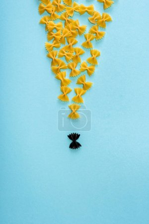 Photo for Top view of unique black pasta among yellow on blue background - Royalty Free Image