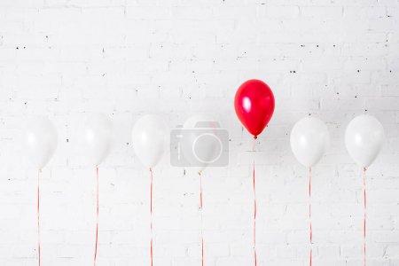 Foto de Globo rojo único entre otro sobre fondo blanco - Imagen libre de derechos