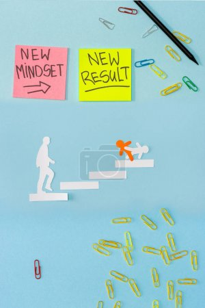Photo for Top view of sticky notes with new mindset and new result lettering with paper clips, pencil and decorative men on career ladder on blue - Royalty Free Image