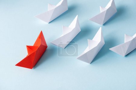 High angle view of unique red paper boat among white on blue