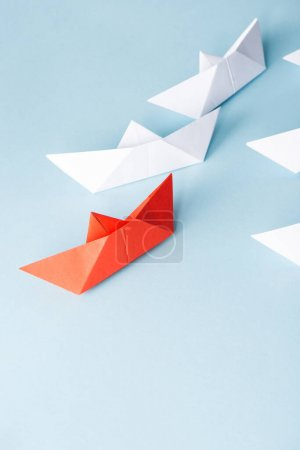 High angle view of unique red paper boat among white on blue background