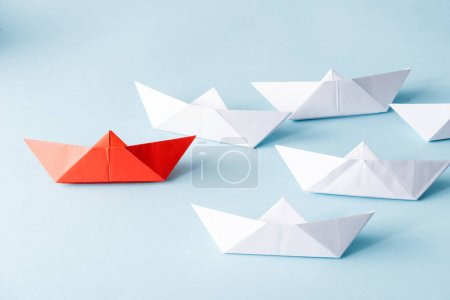 Photo for Unique red paper boat among white on blue background - Royalty Free Image