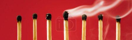 Foto de Único partido quemado con humo entre otros en rojo, disparo panorámico. - Imagen libre de derechos